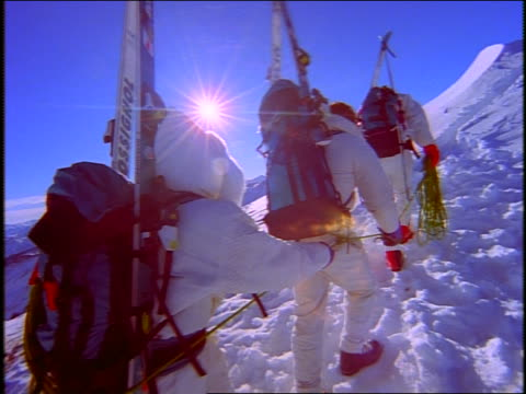 close up point of view following 4 skiers climbing up snowy mountainside