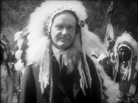 B/W 1927 close up pokerfaced Calvin Coolidge wearing headdress in Sioux tribal ceremony / newsreel