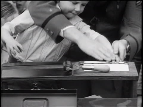 b/w 1936 close up policeman fingerprinting little boy at table / crowd of children in background / newsreel - newsreel stock videos & royalty-free footage
