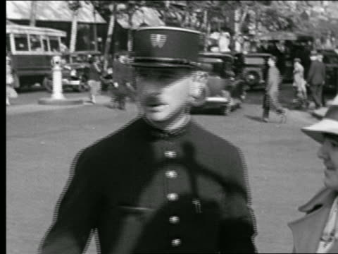 vidéos et rushes de b/w 1936 close up policeman giving woman directions / traffic + people walking in background / paris, france - police