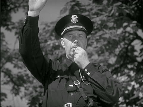 b/w 1951 close up policeman in street blowing whistle + stopping traffic - trillerpfeife stock-videos und b-roll-filmmaterial