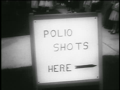 b/w 1955 close up polio shots here sign outdoors / newsreel - polio stock videos & royalty-free footage