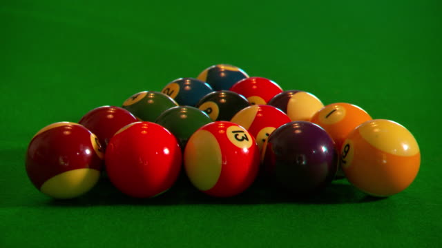 vídeos de stock e filmes b-roll de close up pool balls in green felt table grouped in pre game start position cue ball breaks and scatters balls - mesa de bilhar