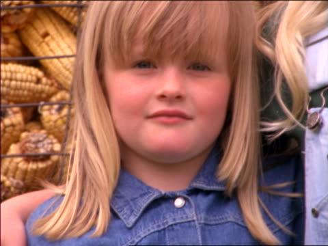 stockvideo's en b-roll-footage met close up pan portrait 2 blonde girls standing in front of pile of corn - alleen meisjes