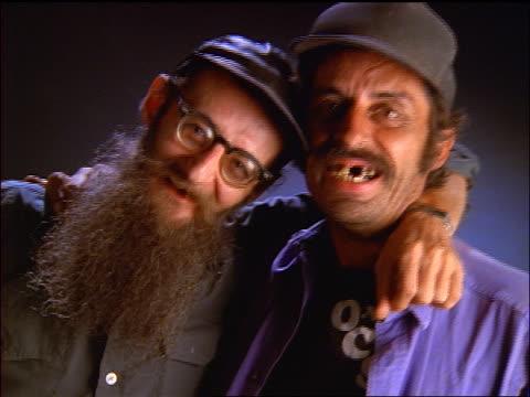 close up portrait pan 2 hillbillies hugging + smiling for camera - ヒルビリー点の映像素材/bロール