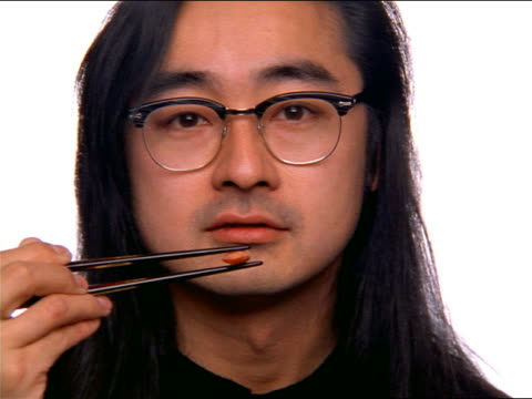 close up PORTRAIT Asian man with long hair + eyeglasses holding small object in chopsticks in front of face