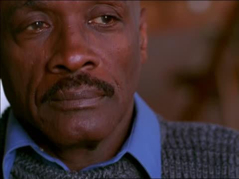 vídeos de stock, filmes e b-roll de close up portrait bald black man with mustache looking off screen / shifts gaze to camera - viúvo