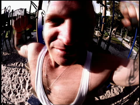 fisheye close up portrait bald man with tattoos posing + flexing muscles for camera in playground / miami - 完全に禿げている頭点の映像素材/bロール