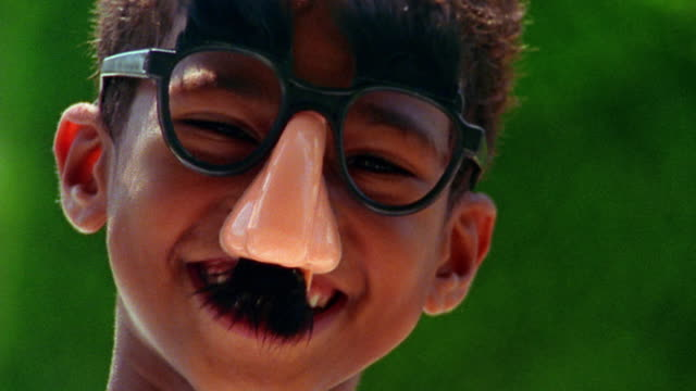 shaky close up portrait black boy wearing joke glasses + laughing outdoors / florida - groucho marx stock videos & royalty-free footage