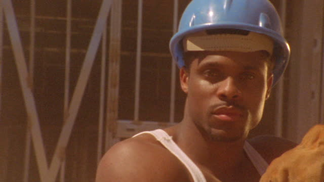 close up PAN PORTRAIT Black construction worker wearing hard hat with heavy dust