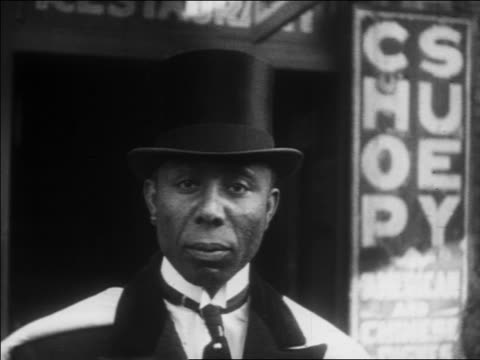 b/w 1930 close up portrait black man in top hat + tuxedo looking at camera / harlem, nyc / newsreel - 1930点の映像素材/bロール