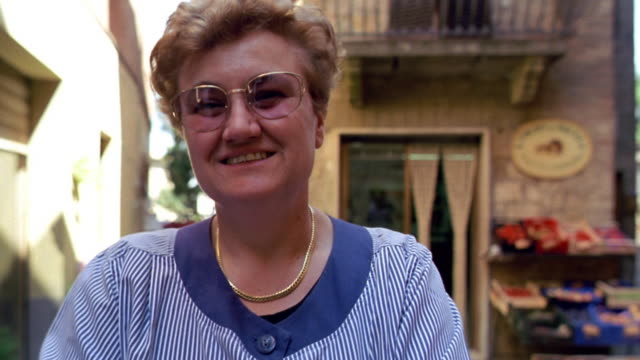 close up PORTRAIT blond Italian woman standing in front of produce stand smiling / Pienza, Italy