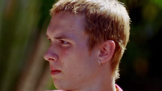 close up portrait blond teen boy turning head to camera outdoors - one teenage boy only stock videos & royalty-free footage