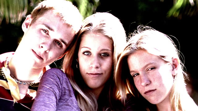 overexposed close up portrait blond teen boy + two blond teen girls outdoors - maschio con gruppo di femmine video stock e b–roll