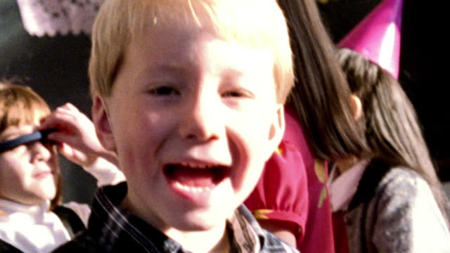 overexposed close up portrait blonde boy smiling at camera at party / other children in background - overexposed video stock e b–roll