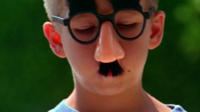 shaky close up portrait blonde boy wearing joke glasses + making faces outdoors / florida - groucho marx stock videos & royalty-free footage