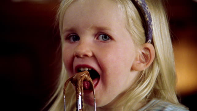 close up PORTRAIT blonde girl licking choclate frosting/cake mix from electric mixer beater