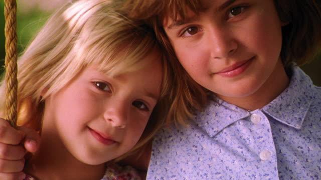 close up PORTRAIT blonde girl resting head on other girl's shoulder smiling outdoors