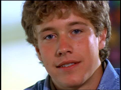 stockvideo's en b-roll-footage met close up portrait blonde teen boy smiling at camera indoors - alleen één tienerjongen