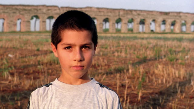 close up portrait boy standing in field looking serious then smiling / aqueduct in background / italy - italian culture stock-videos und b-roll-filmmaterial