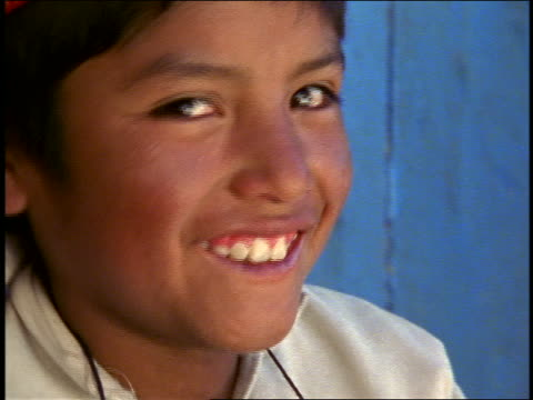 stockvideo's en b-roll-footage met close up portrait boy with red cap sitting near blue wall smiling  / isla taquile, lake titicaca - peruaanse etniciteit