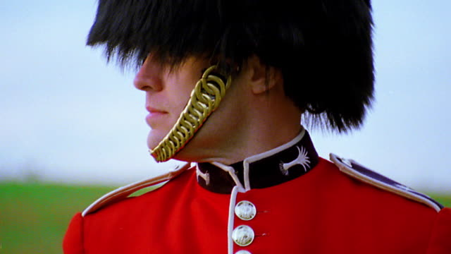 close up portrait buckingham palace guard looking to side then turning head to camera / london, england - 近衛兵点の映像素材/bロール