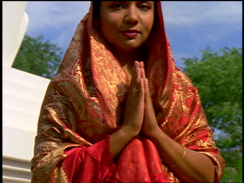vídeos y material grabado en eventos de stock de close up portrait dolly shot tilt up east indian woman in sari standing with hands in prayer position in front of stupa - una sola mujer madura