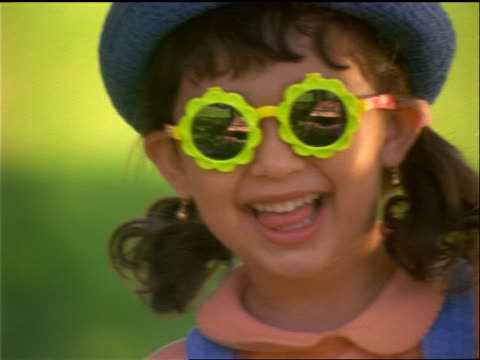 close up PORTRAIT face of Hispanic girl in hat wearing funny sunglasses