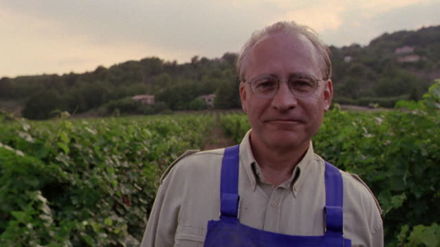 close up portrait pan farmer standing in vineyard smiling surrounded by vines / st. emilion, france - produttore video stock e b–roll
