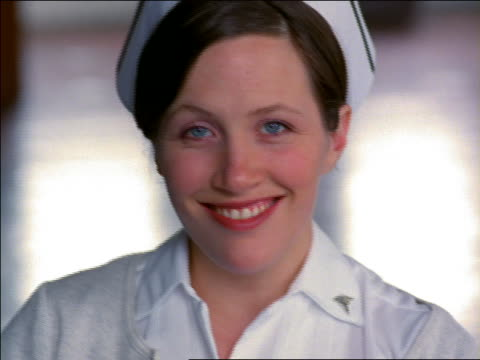 close up portrait female nurse in uniform smiling at camera - uniform stock videos & royalty-free footage