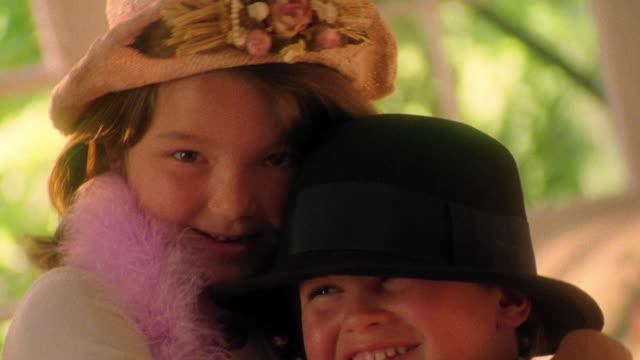 vídeos de stock, filmes e b-roll de close up portrait girl + boy in hats + dress-up clothes hugging + laughing indoors - irmão