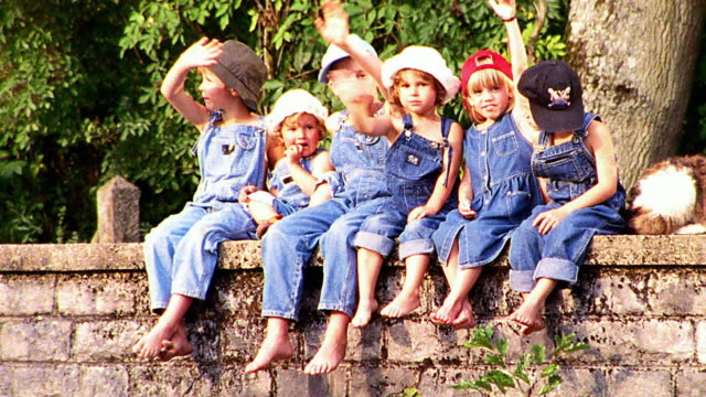 close up PAN PORTRAIT group of children in overalls sitting on bridge waving to camera