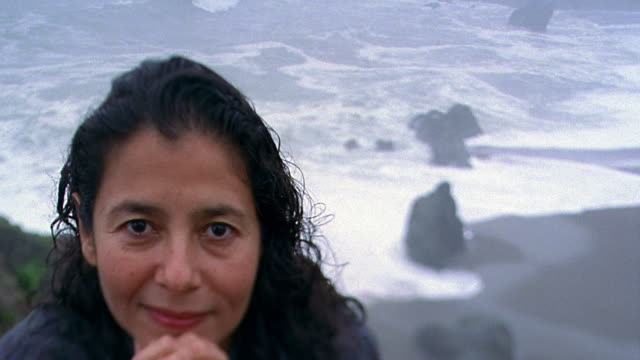 Close up portrait Hispanic woman smiling / waves crashing on beach below in background / California
