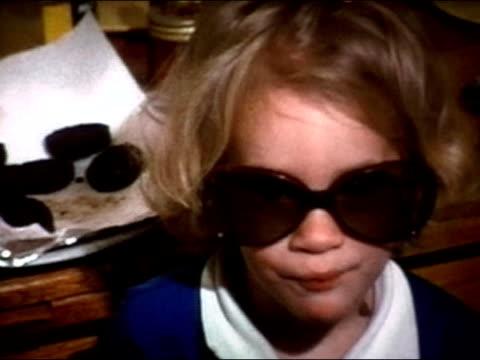 vidéos et rushes de 1975 close up portrait little girl playing with big sunglasses and pacifier - seulement des petites filles