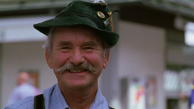 close up portrait man smiling +  wearing german hat + lederhosen / people in background / munich, germany - baviera video stock e b–roll