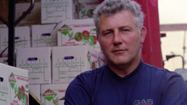 close up PORTRAIT man standing with arms crossed in front of truck loaded with boxes of food / Dublin, Ireland