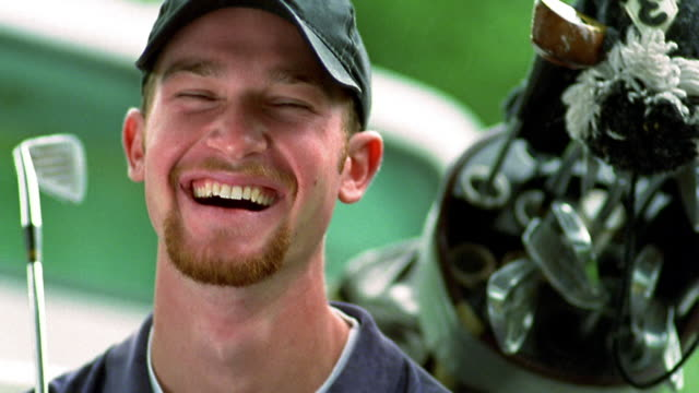 close up portrait man with beard in baseball cap, holding golf club and smiling / bag of clubs in background / ca - baseball cap stock videos & royalty-free footage