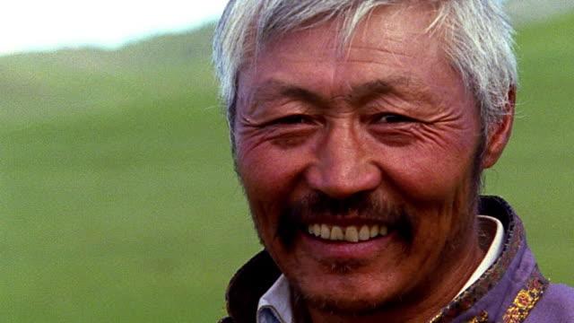 vidéos et rushes de close up portrait middle-aged asian man smiling outdoors / mongolia - mongolie indépendante