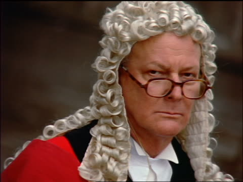 close up PORTRAIT middle-aged barrister in wig turning to look at camera / London