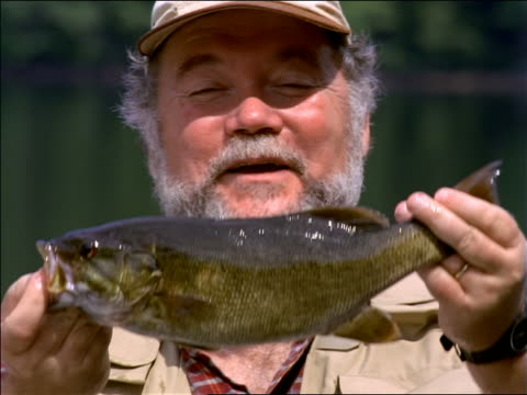 close up portrait middle-aged fisherman with beard smiling, holding up + admiring fish he caught - only mature men stock videos & royalty-free footage