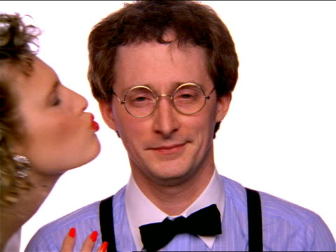 close up portrait nerdy man in eyeglasses looking at camera + getting kiss from woman / looks shocked - geek stock videos and b-roll footage