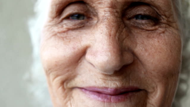 Close up portrait of a happy senior woman smiling. Handheld shot