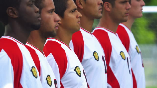 Soccer players stand together in a row while one looks over with a look of fierce determination.