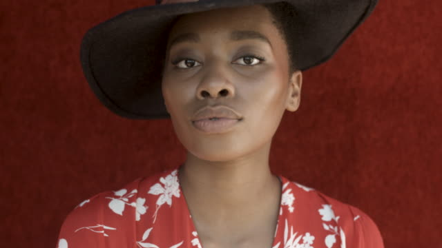 close up, portrait of african-american woman with hat on red background - fashionable stock videos & royalty-free footage