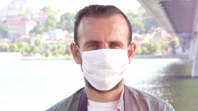 vídeos de stock, filmes e b-roll de close-up retrato de belo jovem millennial dos anos 40 cobrir seu rosto usando máscara branca médica facial, anti-coronavírus covid-19 proteção contra surtos de doenças infecciosas pandêmicas, conceito de saúde, vídeo 4k. - anti higiênico