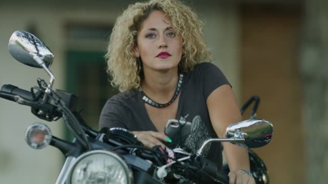 close up portrait of beautiful woman sitting on motorcycle / payson, utah, united states - payson stock-videos und b-roll-filmmaterial