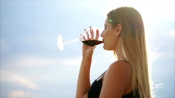 Close up portrait of charming woman drinking wine on the terrace.