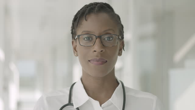 close up portrait of confident female black doctor standing in hospital corridor looking at camera with stethoscope - one mid adult woman only stock videos & royalty-free footage