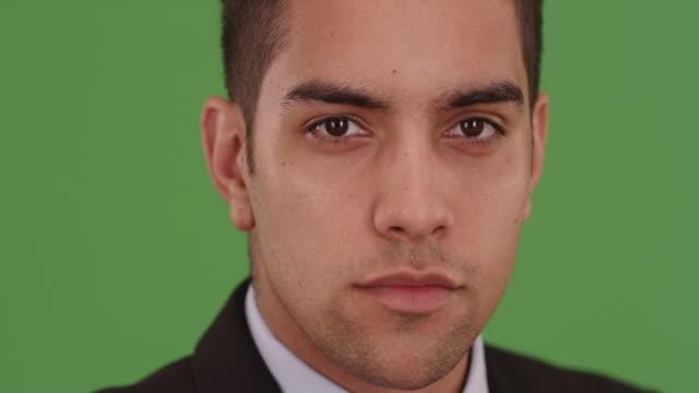 vídeos de stock, filmes e b-roll de close up portrait of confident latino businessman on green screen - neckwear