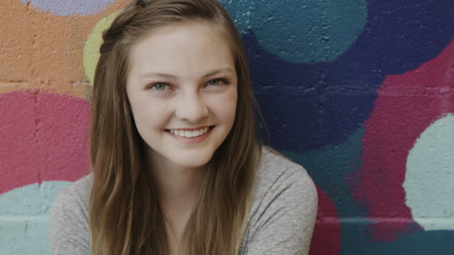 close up portrait of confident smiling girl posing near dotted wall / provo, utah, united states - provo stock videos & royalty-free footage